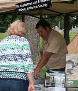 Reuben Moss discusses artifacts with a visitor at Middletown