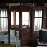 Interior of 168 with sliding doors closed.  Original interior paneling was removed decades ago. but the original varnish is visible on some of the woodwork here.